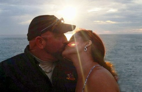 Man with baseball cap and women with long brunette hair kissing in front of the setting sun