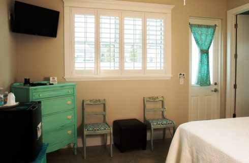 Corn of guest room with pale walls, teal dresser, two chairs and a large bright window.