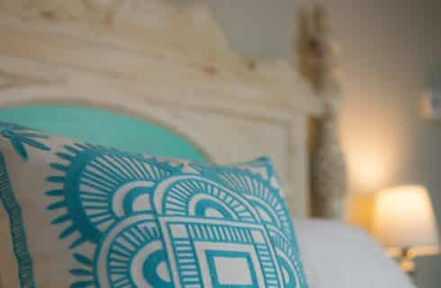 Closeup of white distressed headboard and teal and white pillows.