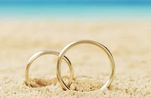Large and small gold wedding bands nestled in the sand with blue ocean in background.