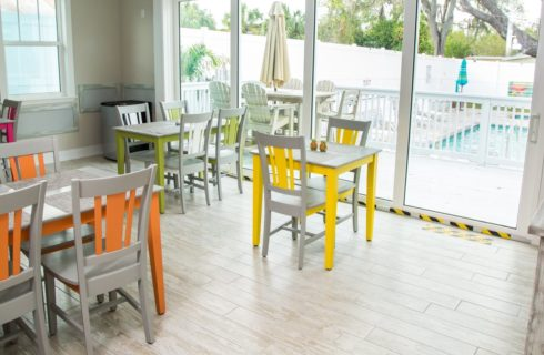 Breakfast room with tile floor and colorful tables and chairs.
