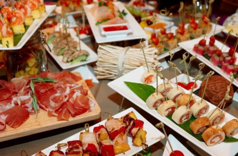 Assorted finger foods, with pinwheels, kabobs and charcuterie.