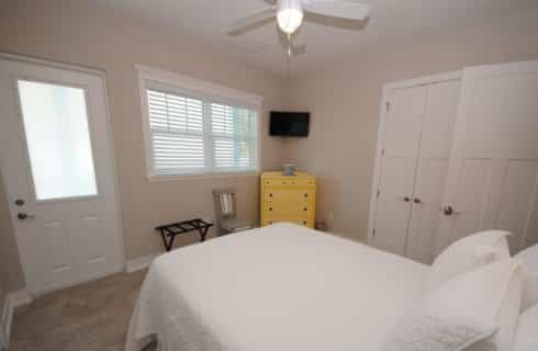GUestroom painted pale peach with bed, dresser and ceiling fan.