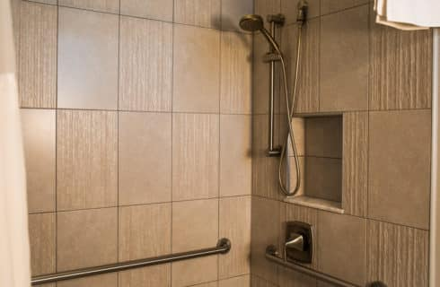 Tiled walk in shower with grab bars and moveable shower head.
