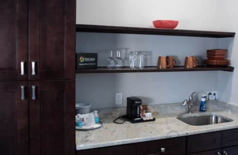 Dark wood kitchenette area with granite counter, sink, and cabinet and shelf storage.