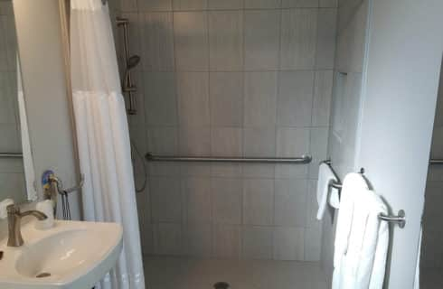 Roll-in shower with grab bars, adjustable shower head and white shower curtain.