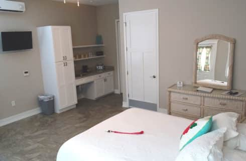 Large bedroom with white bed, dresser with mirror and plenty of floor space.