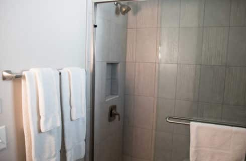 Shower enclosure with peach and white tiles next to towels on a rack.