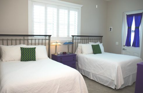Twin Beds with iron headboards made up in white sit under a window with a nightstand holding lamps between them.