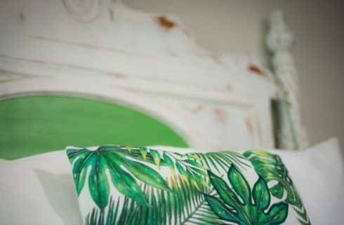 Closup of white bed with a green headboard medallion and a palm print throw.