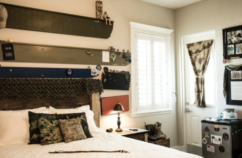 Bedroom with white bed and several pieces of military memorabilia.