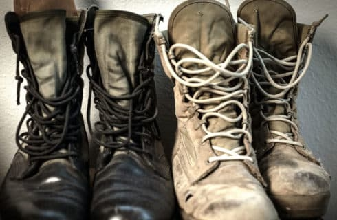Two pair of worn combat boots, one black and one desert tan.