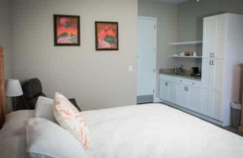 Bedroomw ith beige walls, white bedding, kitchenette and sunset paintings.