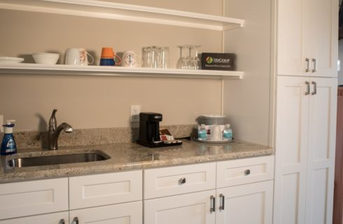 White kitchenette area with granite counter, sink, and cabinet storage.