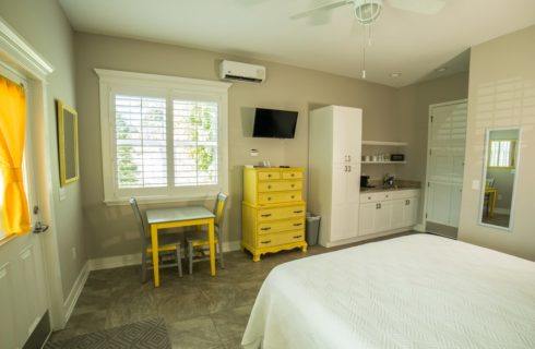 Bright bedroom with a bed mad eup in white with yellow furniture and decor.