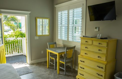 Yelow dresser and yellow and grey table and chairs in guest cottage near door.