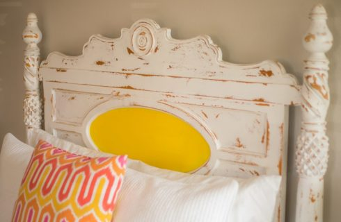 Shabby Chich headboard win whitewash with a sunshine yelow medallion.