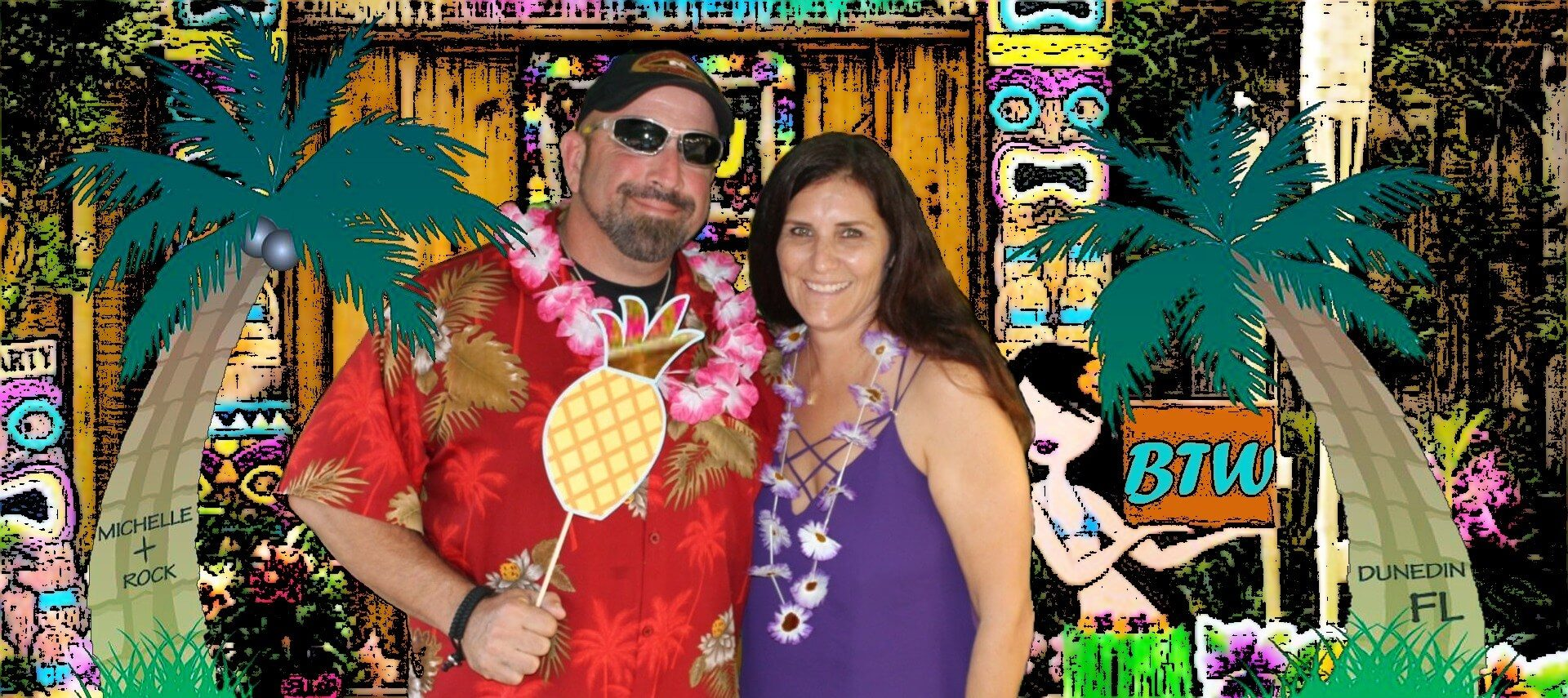 Couple dressed in tropical clothing staniding in front of a Tiki hut