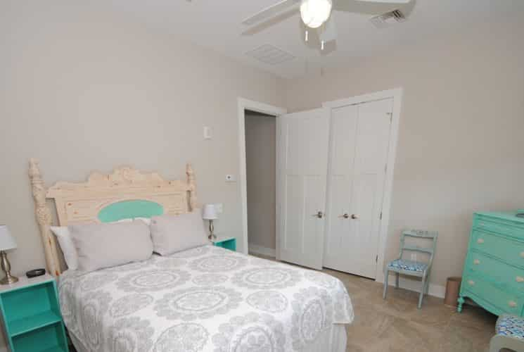 Guest room with farmhouse bed mad up in white and teal, teal dresser and nightstand and TV on wall.