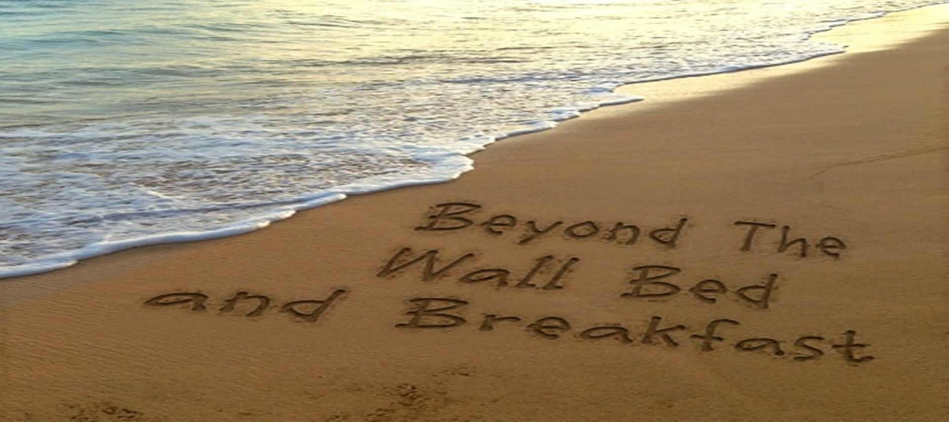 Waves lapping at sand beach with words in teh sand: Beyond the Wall Bed and Breakfast