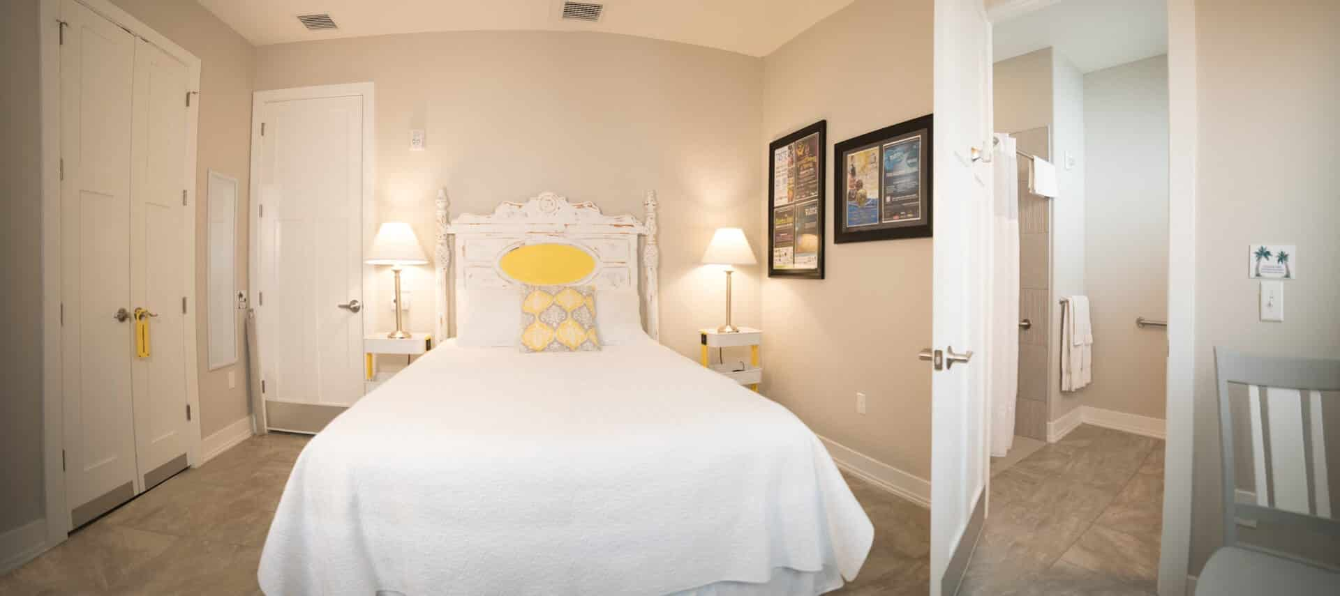 Large bed with shabby chic headboard made up in white bedding has nighstands on both sides with lamps.