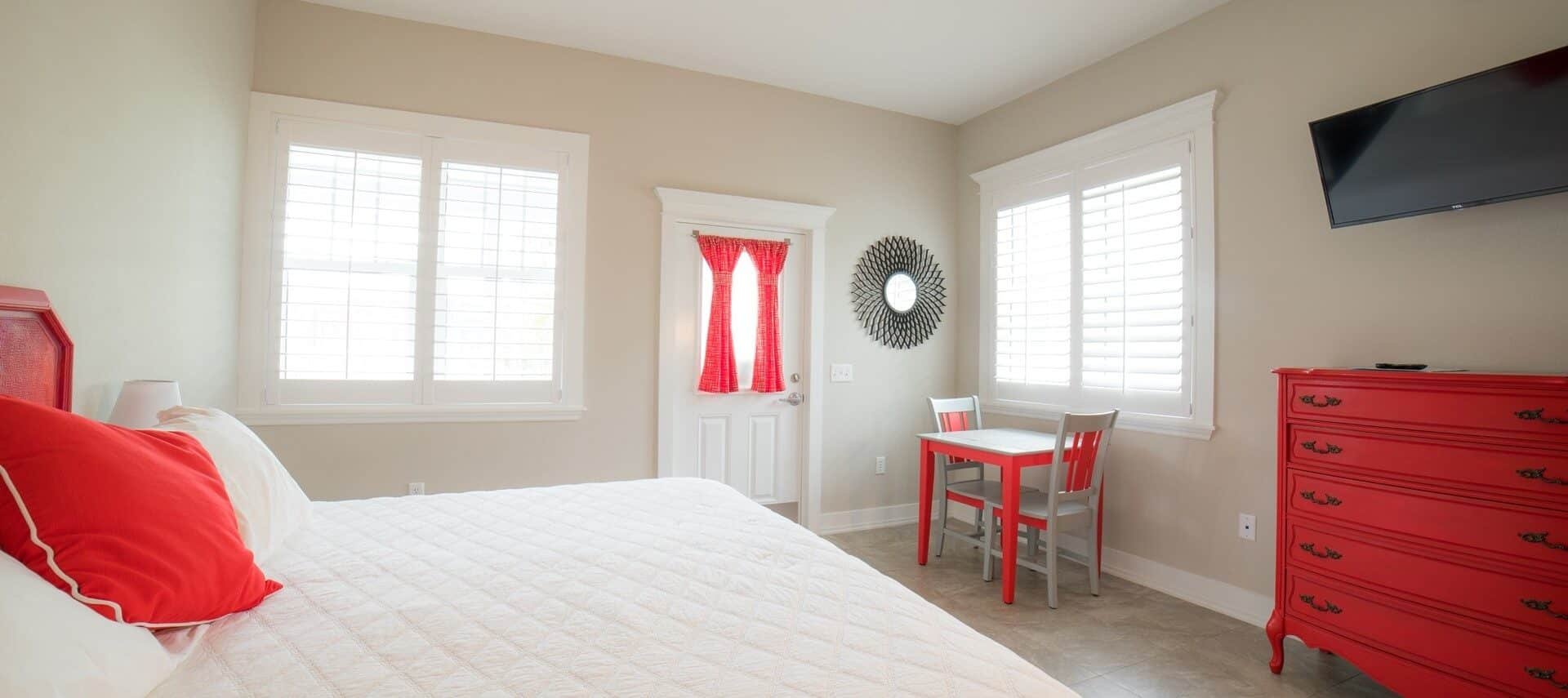 Guest room in white and beige with orangey-red accents and furnishings.