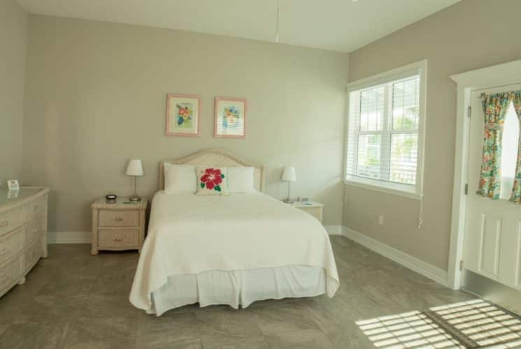 Large bright and airy bedroom with a bed made u pin white, dresser with mirror and windows.
