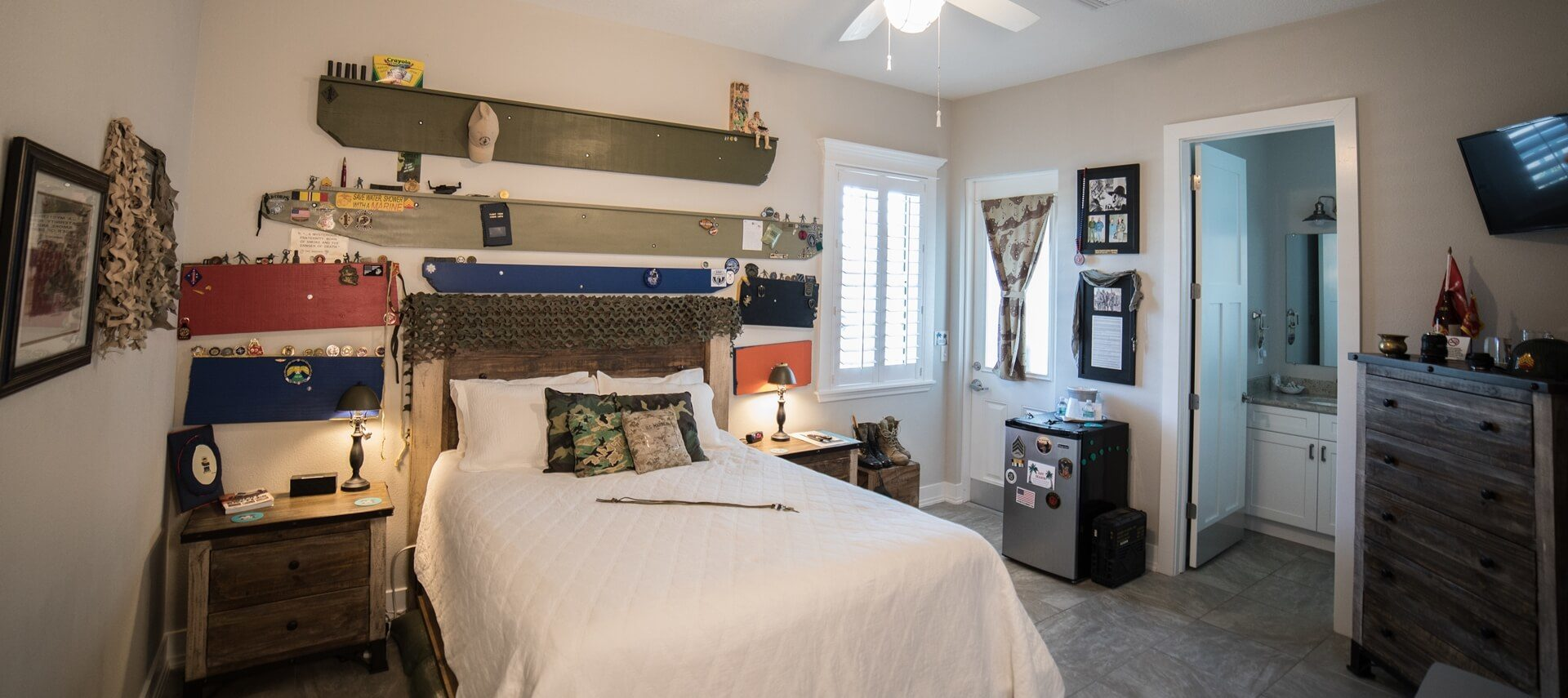 Guestroom with bed made up in white, shelves with military memorabilia, dresser and TV on the wall.