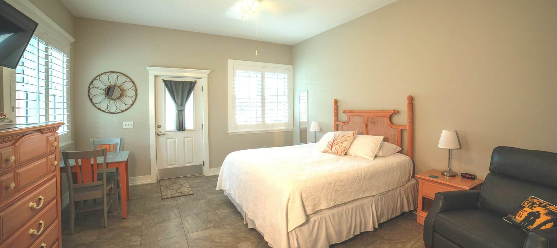 Bright and airy bedroomw ith a bed made up in white, coral -colored dresser, and TV on wall.