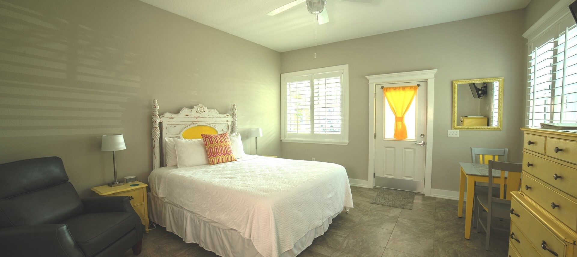 Braight and airy guestroom with a Bed amde up in white, a yellow dresser and a ceiling fan.