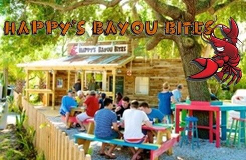 People sitting at picnic tables outside of a restaurant Happy's Bayou Bites.