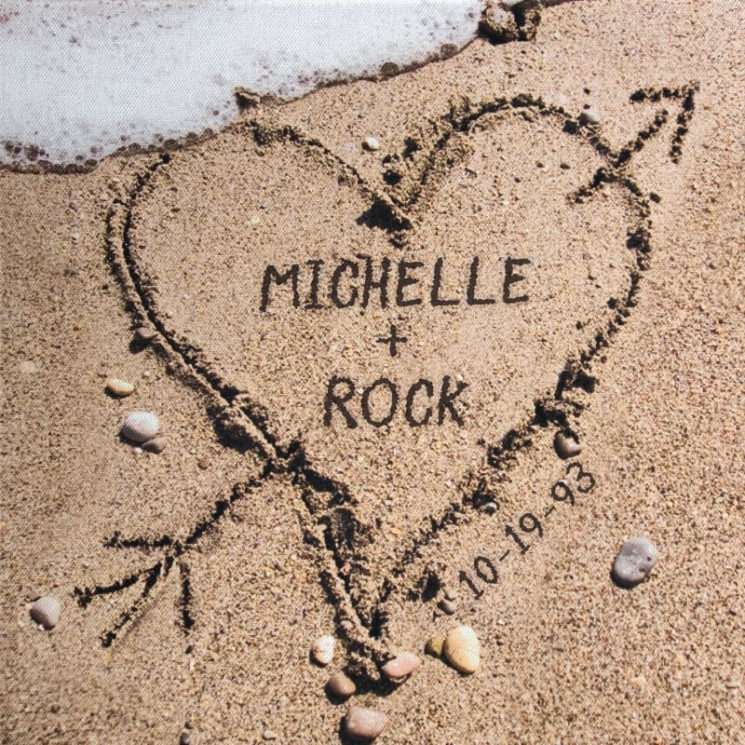 Michelle & Rock inside a heart in the sand on the shore